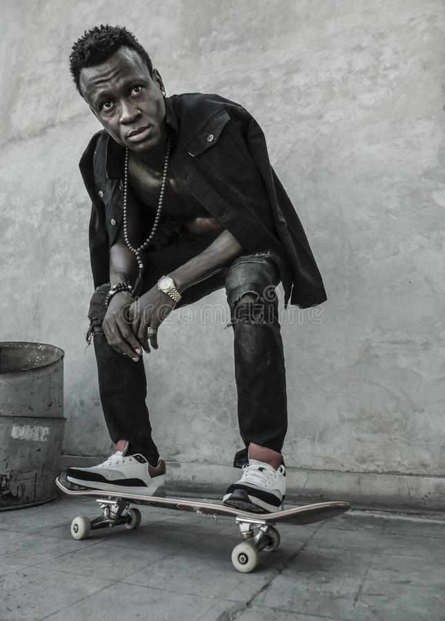 Young attractive and serious black afro American man squatting on skate board at grunge street corner looking cool posing in. Urban lifestyle portrait of young stock photos