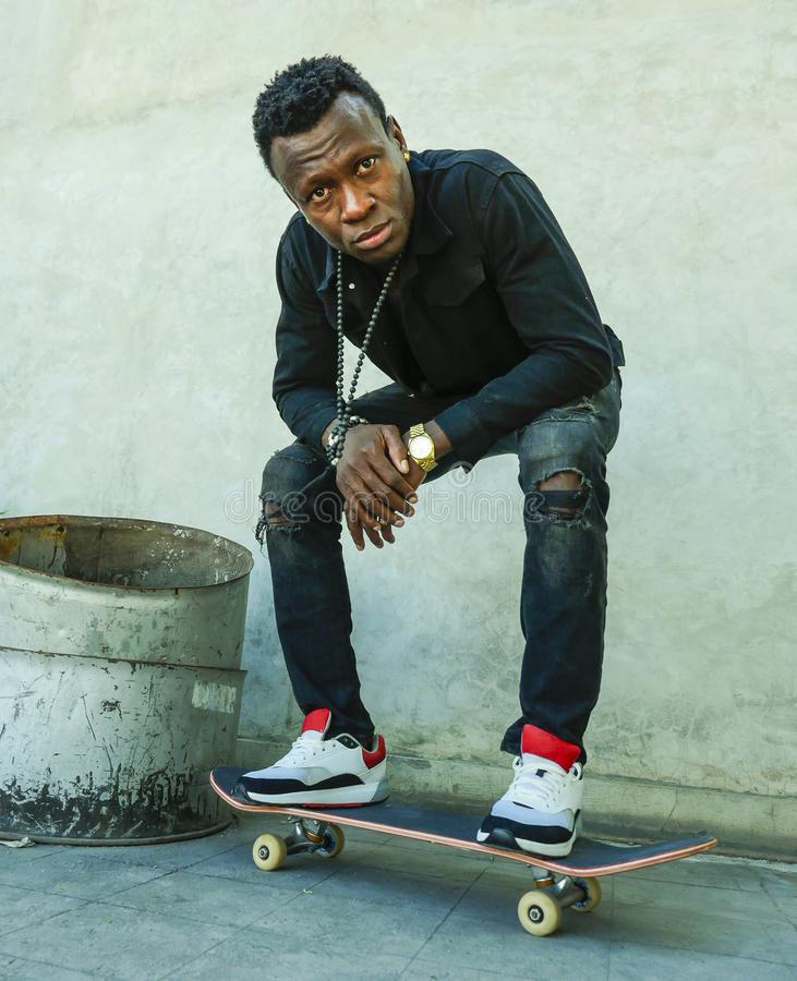 Young attractive and serious black afro American man squatting on skate board at grunge street corner looking cool posing in. Urban lifestyle portrait of young royalty free stock images