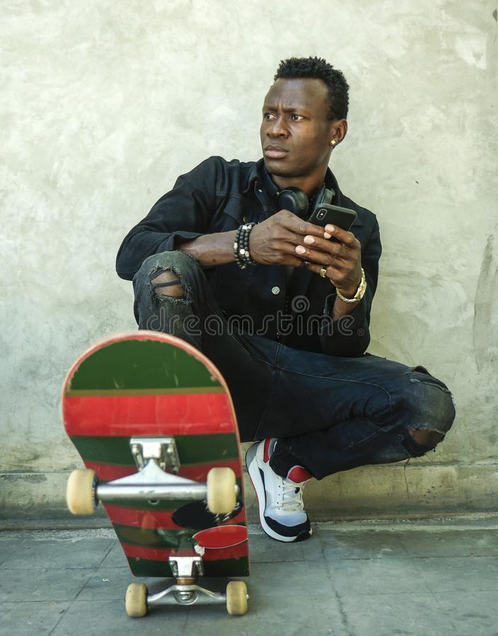 Young attractive and serious black afro American man squatting on skate board at grunge street corner posing in badass bad boy. Urban lifestyle portrait of young royalty free stock image