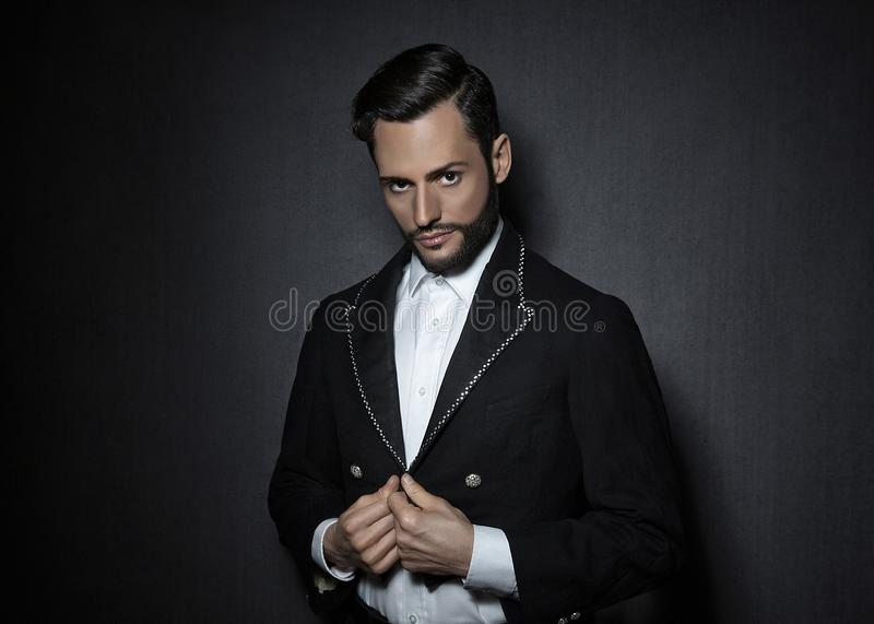 Young attractive, sexy man with beard, dressed in a circus look jacket stock photo
