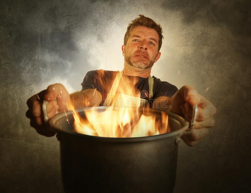 Young attractive and shocked messy home cook man with apron holding cooking pot in fire burning the food in kitchen disaster stock photos