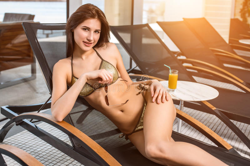 Young attractive slim girl in bikini relaxing on deck chair in wellness spa hotel resort. Near the table is a glass of orange juice stock image