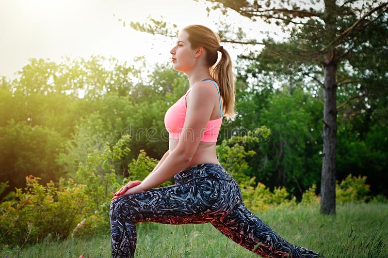 Young attractive slim woman stretching in the park. Healthy lifestyle concept stock photography