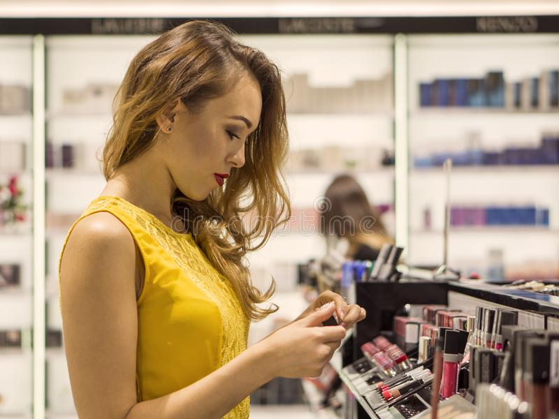 Young Attractive Smiling Girl in Yellow Dress is Choosing new Lipstick in Cosmetics Store stock photography