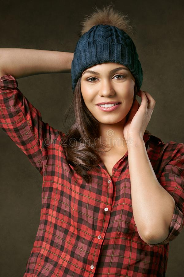 Young, attractive, smiling woman adjusting a winter hat stock photos