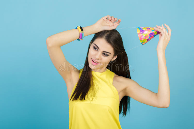 Young attractive smiling woman with birthday hat and whistle on blue background. celebration and party. Young attractive smiling woman with a birthday hat and stock images
