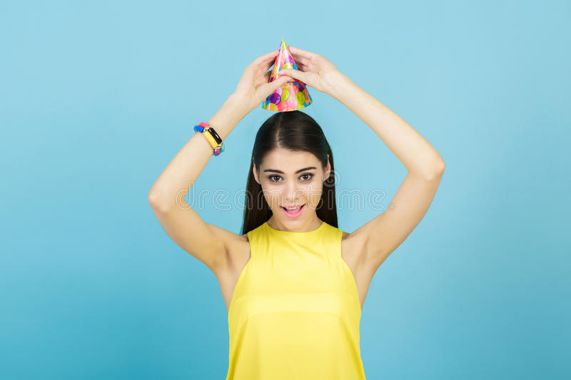 Young attractive smiling woman with birthday hat and whistle on blue background. celebration and party stock image