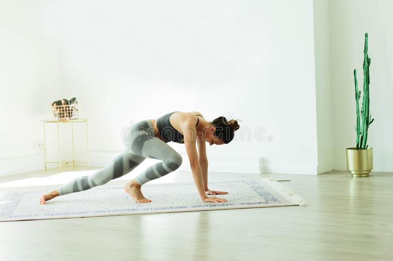 Young attractive smiling woman practicing yoga in a stylish room stock image