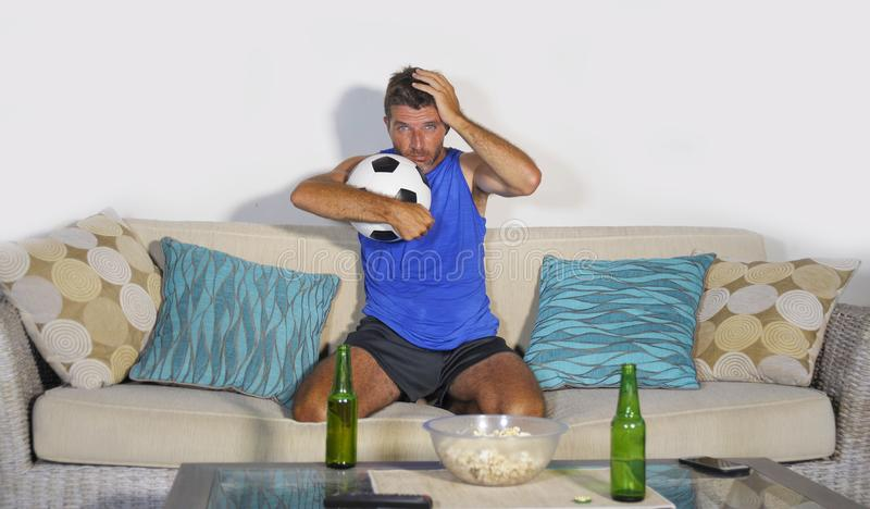 Young attractive soccer fan and supporter man at home sofa couch. Watching football game on TV dejected and sad after team defeat loss and defeat drinking beer royalty free stock photo