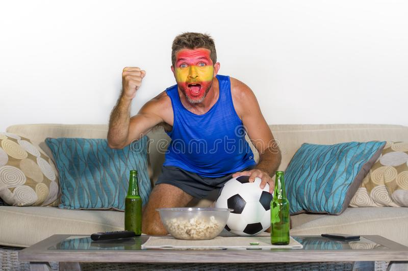 Young attractive Spanish man happy and excited watching football match on TV celebrating victory goal crazy with Spain flag painte stock photo