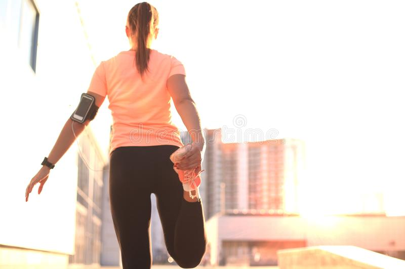 Young attractive sporty fitness woman runner warming up before run at sunset or sunrise on city. stock photography