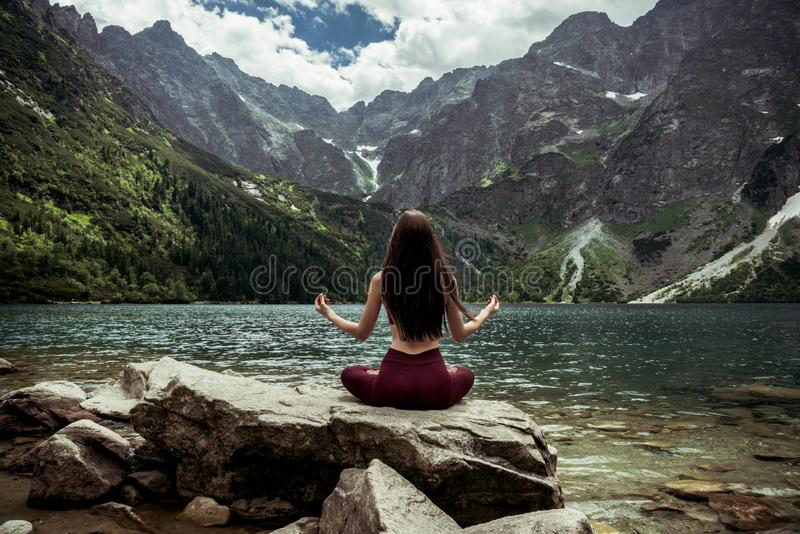 Young attractive sporty girl in dark red sportswear practicing yoga, sitting in Sukhasana pose on big stone in fronte of stock photos