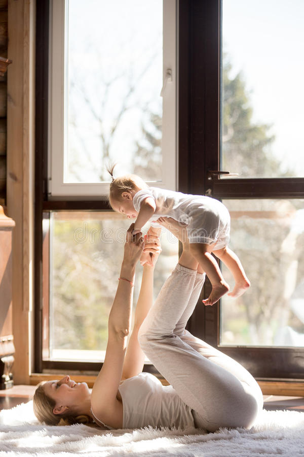 Young attractive sporty mother and baby daughter exercising at h. Young attractive sporty mother working out with her baby daughter, exercising at home wearing stock images