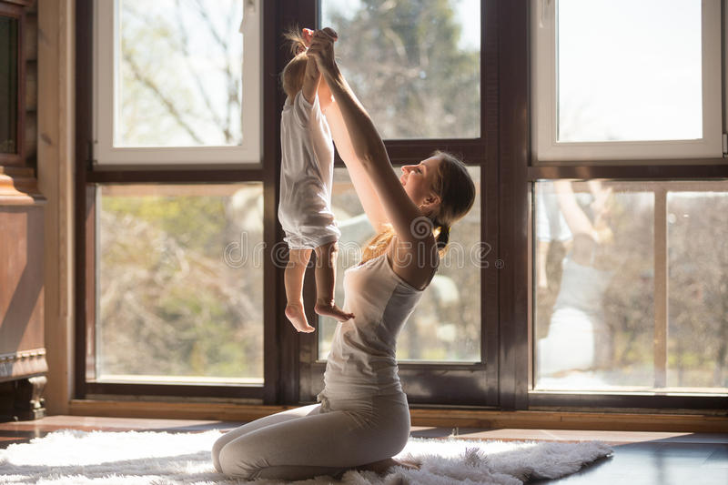 Young attractive sporty mother doing exercises with baby at home royalty free stock image