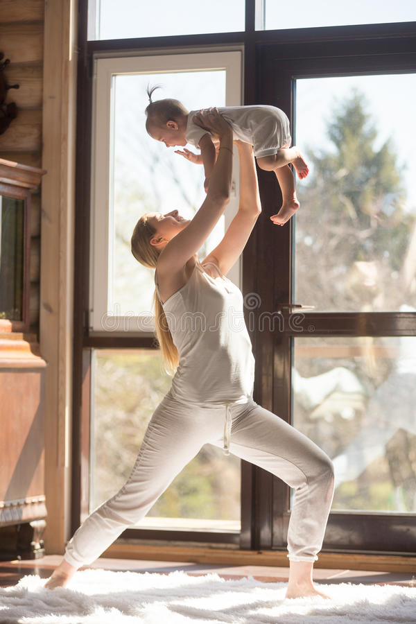 Young attractive sporty mother doing exercises with her baby, ho royalty free stock photos