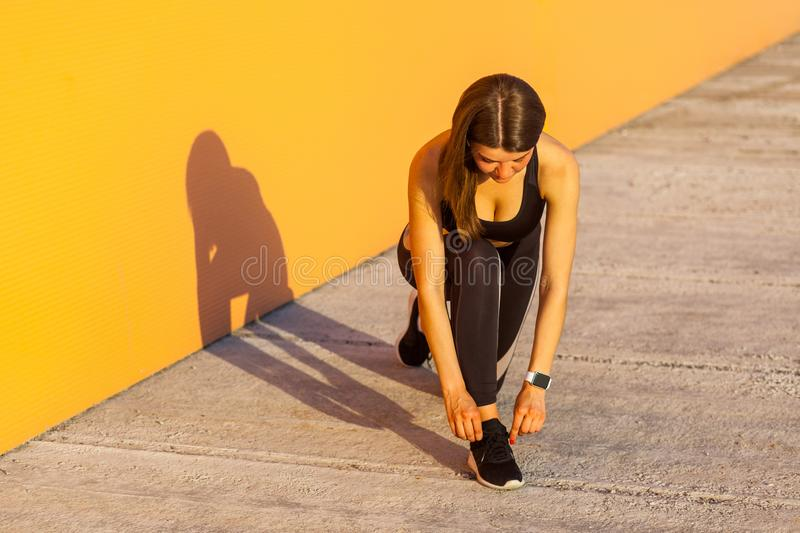 Young attractive sporty woman wearing black sporwear in morning on street standing on knee and preparing for training, tying royalty free stock photo
