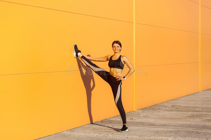 Young attractive sporty woman wearing black sporwear practicing sport exercises in morning on street, showing perfect twine on stock photo