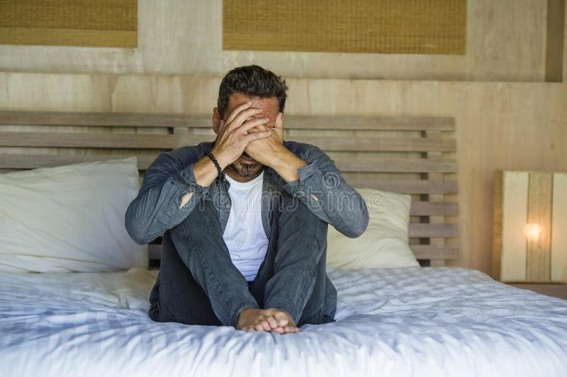 Young attractive stressed and depressed man sitting on bed worried and frustrated suffering depression crisis covering face with stock photography