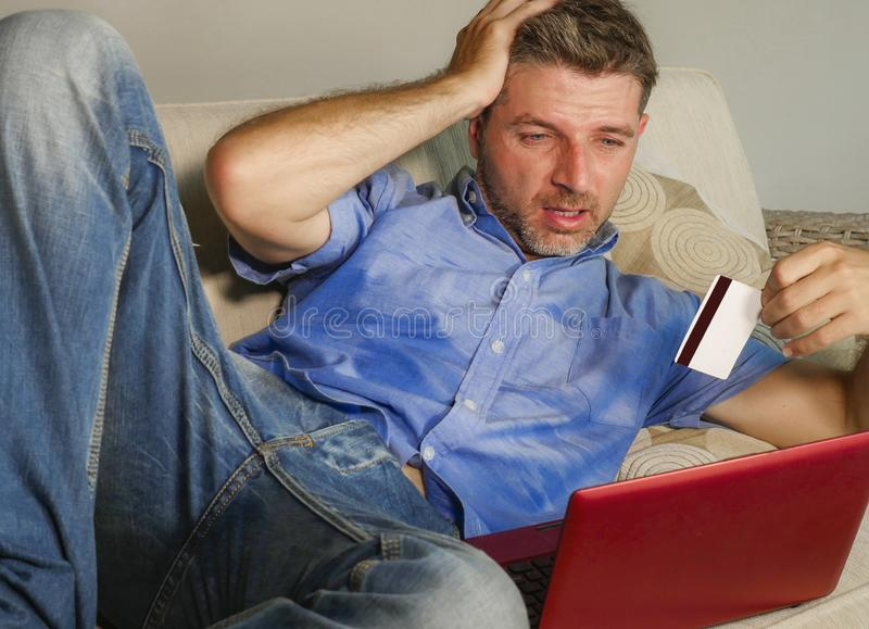 Young attractive and stressed man worried at home sofa couch using credit card and laptop computer suffering problem while banking. In internet business stock images