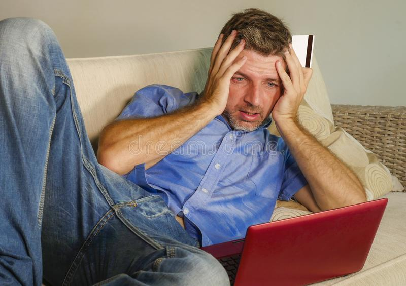 Young attractive and stressed man worried at home sofa couch using credit card and laptop computer suffering problem while banking. In internet business stock photos
