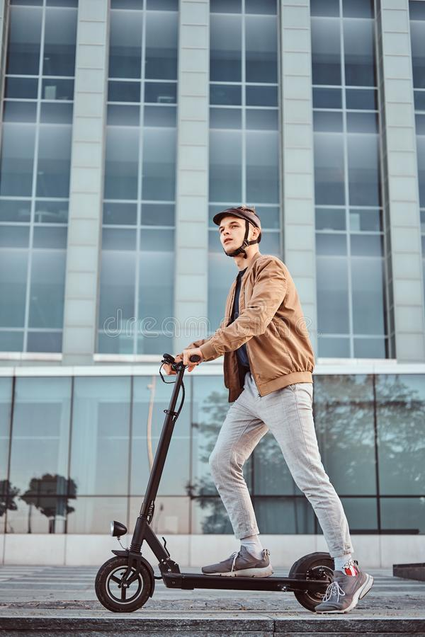 Young man is driving his hew electro scooter. Young attractive student is driving his scooter neat interesting glass building at bright sunny day royalty free stock image