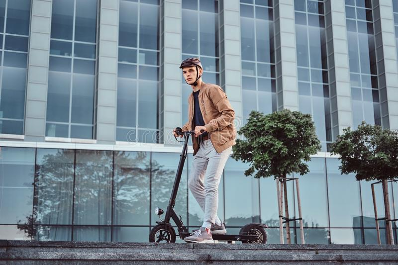 Young man is driving his hew electro scooter stock photography