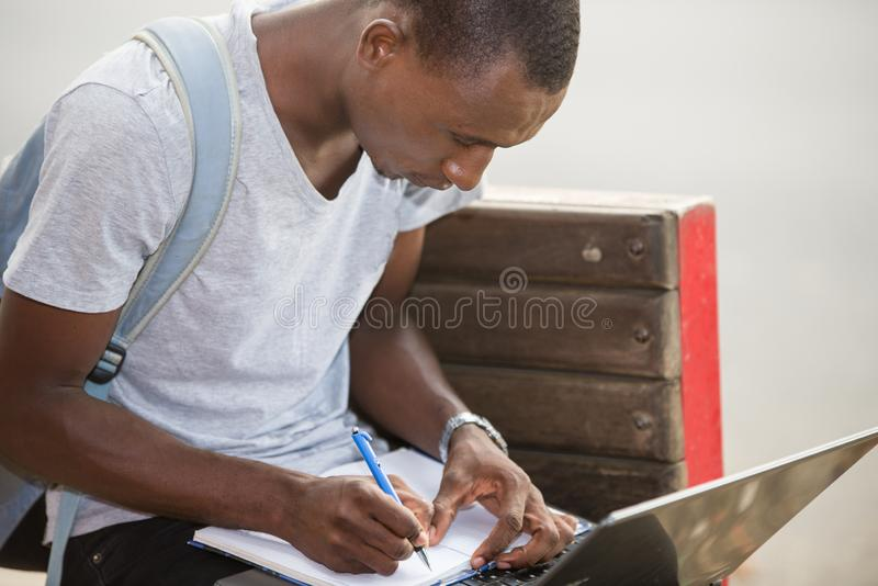 Young male student sitting in city working with laptop and notebook. Young attractive student man in the city working with laptop looking for satisfaction and royalty free stock photos