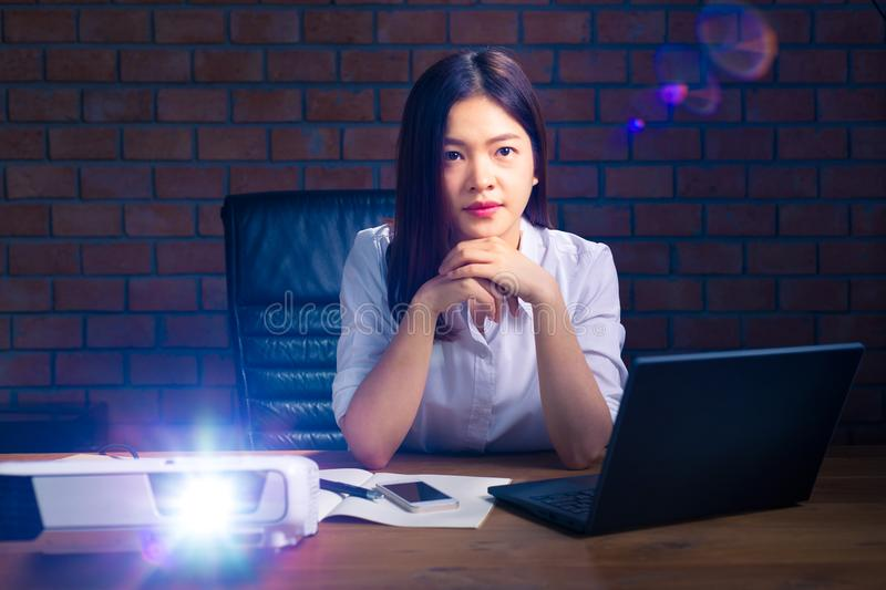 Young attractive asian executive woman watching presentation pro. Young attractive and successful asian executive woman watching presentation projected on screen royalty free stock photo