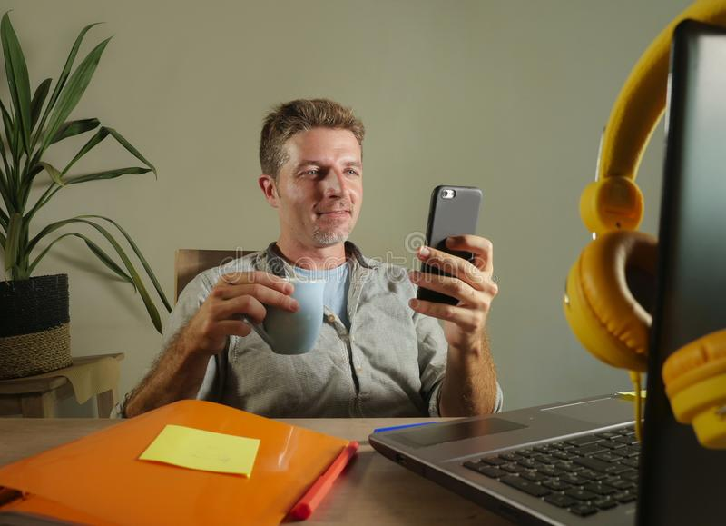 Young attractive and successful self employed business man using mobile phone sending text working at modern home office hispter s royalty free stock image