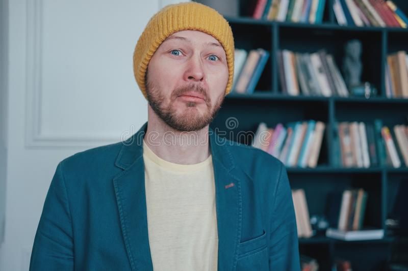 Young attractive surprised man infantile loser hipster in the yellow hat on blue wall library background. The Young attractive surprised man infantile loser stock photo