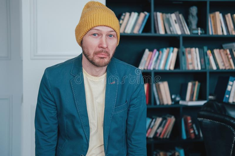 Young attractive surprised man infantile loser hipster in the yellow hat on blue wall library background. The Young attractive fun face man infantile loser stock photos