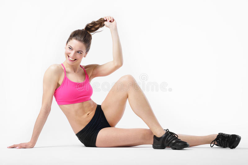 Young attractive tanned slender girl performs sports exercises. royalty free stock photo