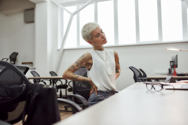 Killful pain. Young attractive tattooed businesswoman with short haircut suffering from back pain while sitting at. Young attractive tattooed businesswoman with stock images