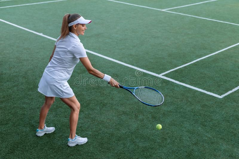 Young attractive tennis player. On the court stock photography