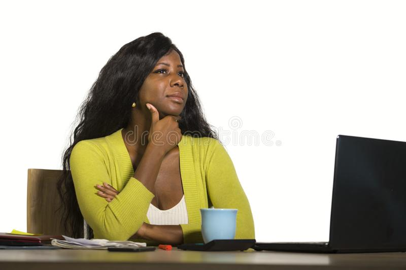 Young attractive and thoughtful black afro American business woman working at office computer desk looking away thinking relaxed i. Solated on white background stock photo