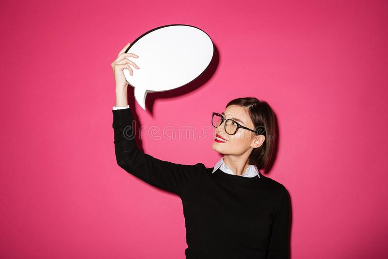 Young attractive thoughtful lady holding and looking at bubble speech stock image