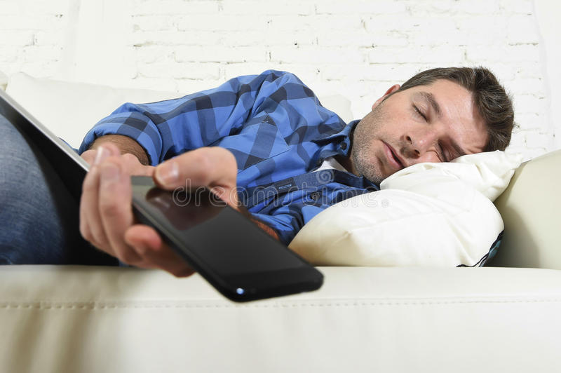Young attractive tired and overworked falling asleep at home couch with mobile phone and digital tablet pad stock images