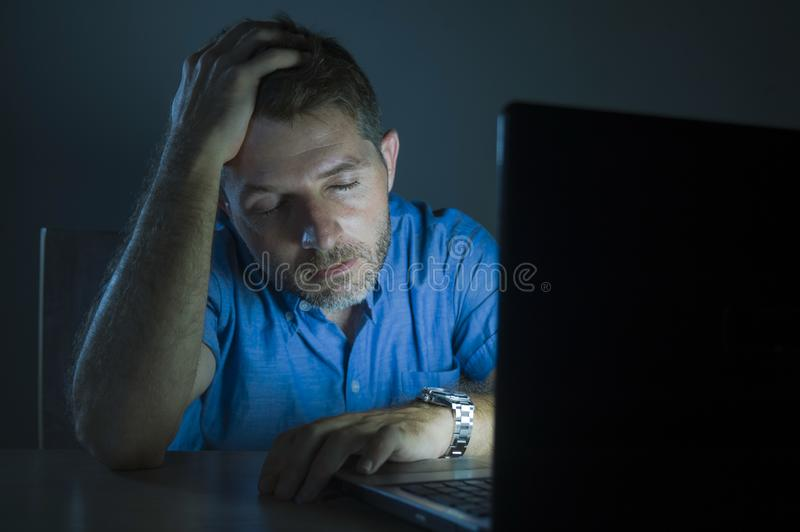 Young attractive and tired unshaven man working late night on laptop computer in the dark feeling frustrated and exhausted in royalty free stock photography