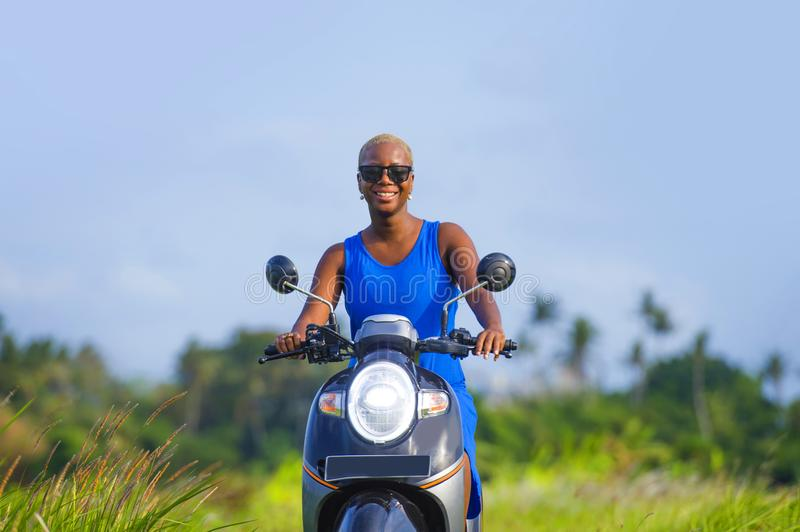 Young attractive tourist afro American black woman riding motorbike happy in beautiful Asia countryside along green rice fields s. Miling free on her scooter in royalty free stock images