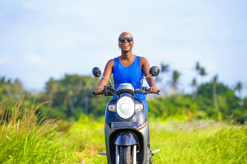 Young attractive tourist afro American black woman riding motorbike happy in beautiful Asia countryside along green rice fields s. Miling free on her scooter in stock images