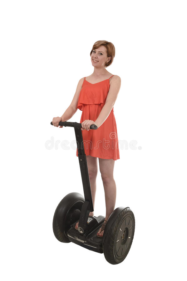 Young attractive tourist woman in chic summer dress smiling happy riding electrical segway. Young attractive tourist woman in chic summer dress smiling happy and stock photography