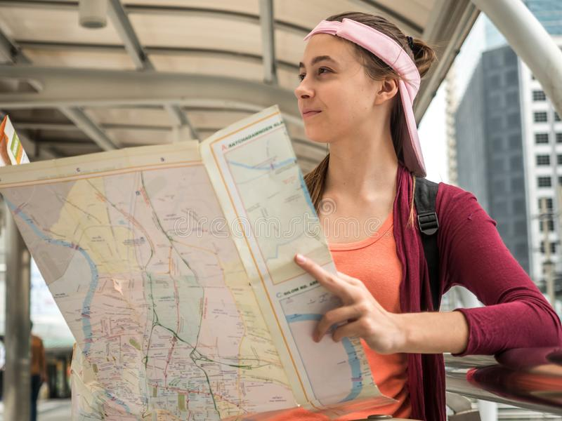 Young Attractive traveler woman holding location map in her hands while looking for some direction on street, travel or exploring royalty free stock image