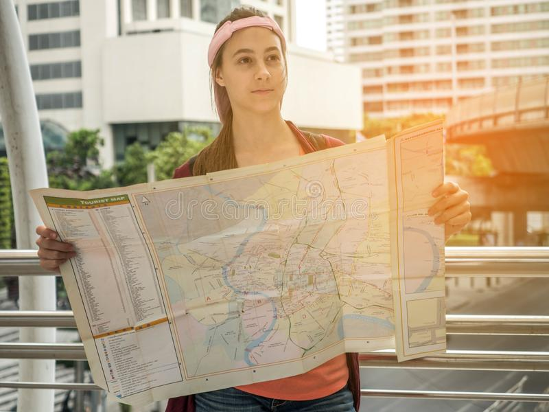 Young Attractive traveler woman holding location map in her hands while looking for some direction on street, travel or exploring stock image