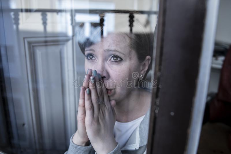 Young attractive unhappy depressed lonely woman looking worried through the window at home royalty free stock image