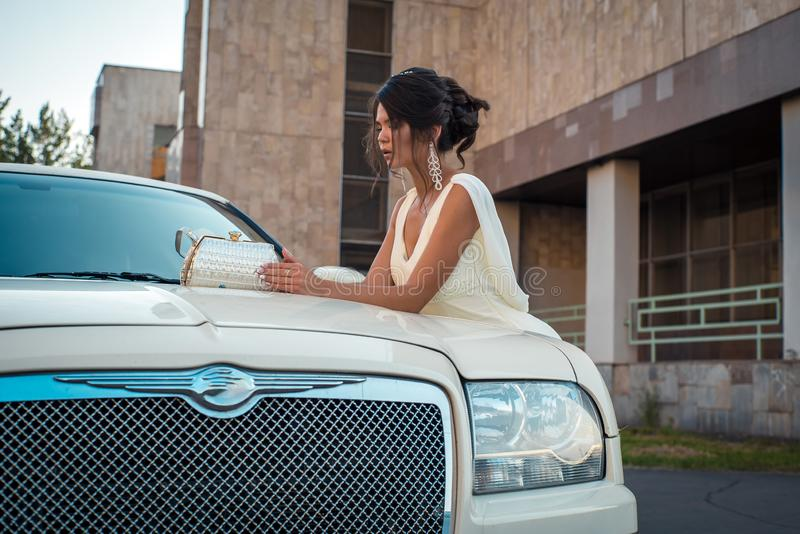 Young attractive VIP Woman in the dress stand near white limousine stock image