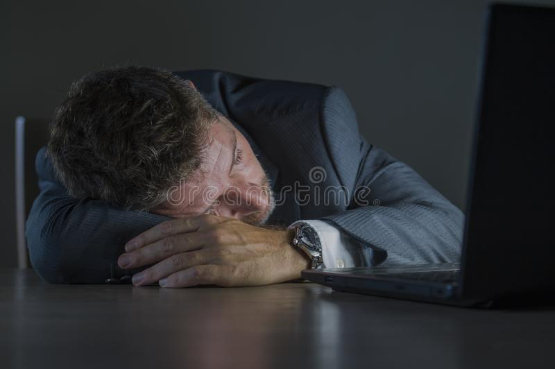 Young attractive wasted and tired entrepreneur man sleeping taking nap late night at office laptop computer desk exhausted in. Financial business problem and royalty free stock photos