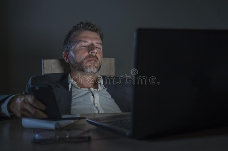 Young attractive wasted and tired entrepreneur man sleeping taking nap late night at office laptop computer desk exhausted in. Young attractive wasted and tired royalty free stock photos