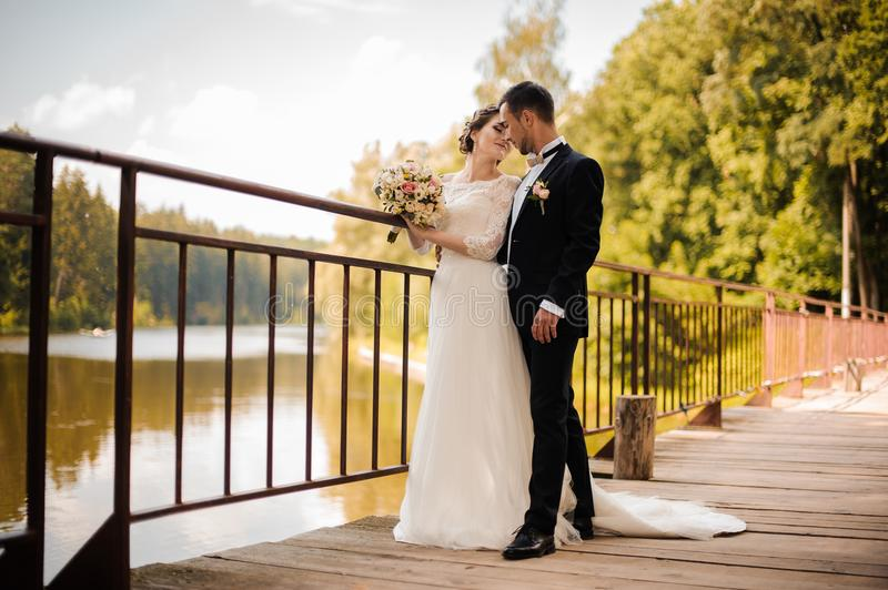 Young and attractive wedding couple on the bridge. Young and attractive wedding couple standing on the wooden bridge against the background of river royalty free stock photos
