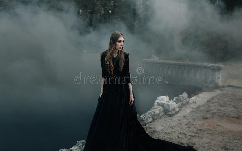 Young attractive Witch walking on the bridge in heavy black smoke. royalty free stock photography
