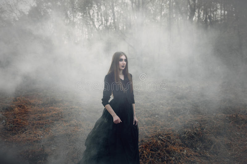 Young attractive Witch walking on the field in heavy black smoke. royalty free stock images
